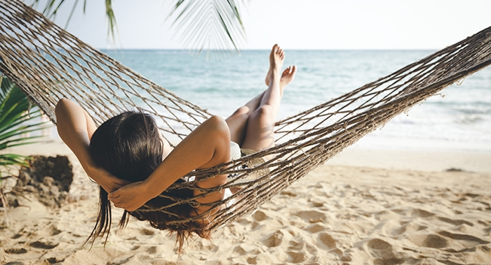 Enjoy relaxing in a hammock on the beach in sunny Treasure Island, Florida.